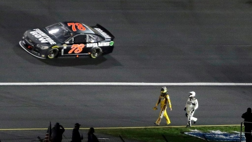 A safety crew worker chases Kyle Busch along the speedway apron after Busch crashed in Turn 3 during the NASCAR Sprint All-Star auto race, as Martin Truex Jr. (78) drives by at Charlotte Motor Speedway in Concord, N.C., Saturday, May 17, 2014. (AP Photo/Gerry Broome)