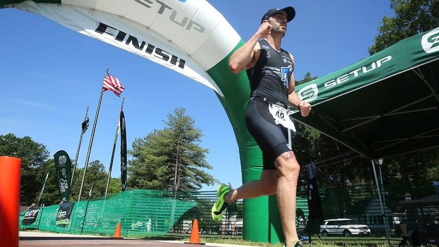 Six-time NASCAR champion driver Jimmie Johnson finishes the Over the Mountain Triathlon in Kings Mountain, N.C., Saturday, May 17, 2014.  (AP Photo/The Star, Ben Earp)
