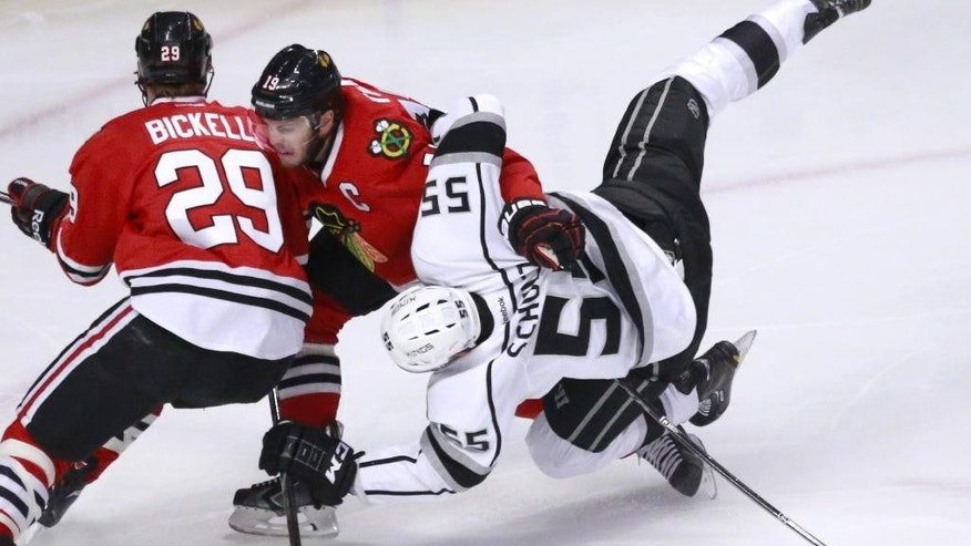 Los Angeles Kings defenseman Jeff Schultz (55) collides with Chicago Blackhawks left wing Bryan Bickell (29) and Jonathan Toews during the first period of Game 1 of the Western Conference finals in the NHL hockey Stanley Cup playoffs in Chicago on Sunday, May 18, 2014. (AP Photo/Charles Rex Arbogast)