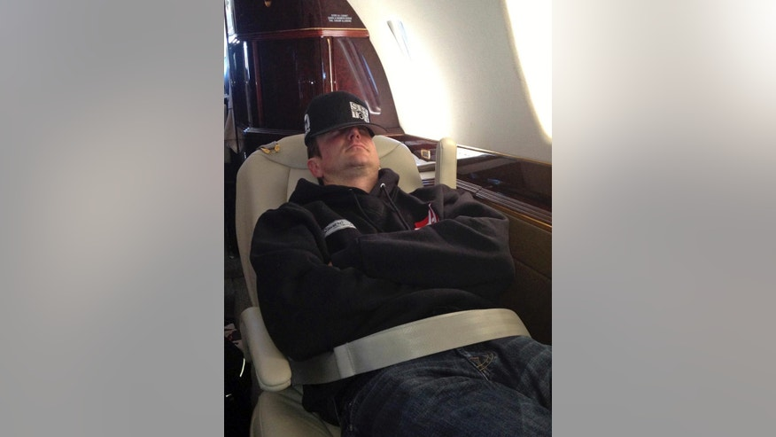 Kurt Busch sleeps on a flight from Indianapolis after qualifying for the Indianapolis 500 to Charlotte Motor Speedway for the NASCAR Sprint All-Star auto race, in Concord, N.C., Saturday, May 17, 2014. (AP Photo/Dan Gelston)