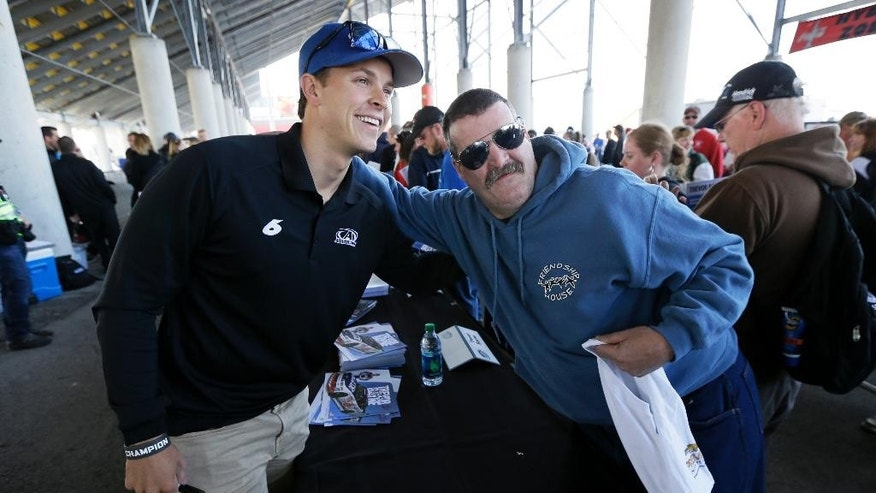 Trevor Bayne poses for a photo with Bob Johnson, of Sioux City, Iowa, right, during an autograph session before the NASCAR Nationwide auto race, Sunday, May 18, 2014, at Iowa Speedway in Newton, Iowa. (AP Photo/Charlie Neibergall)