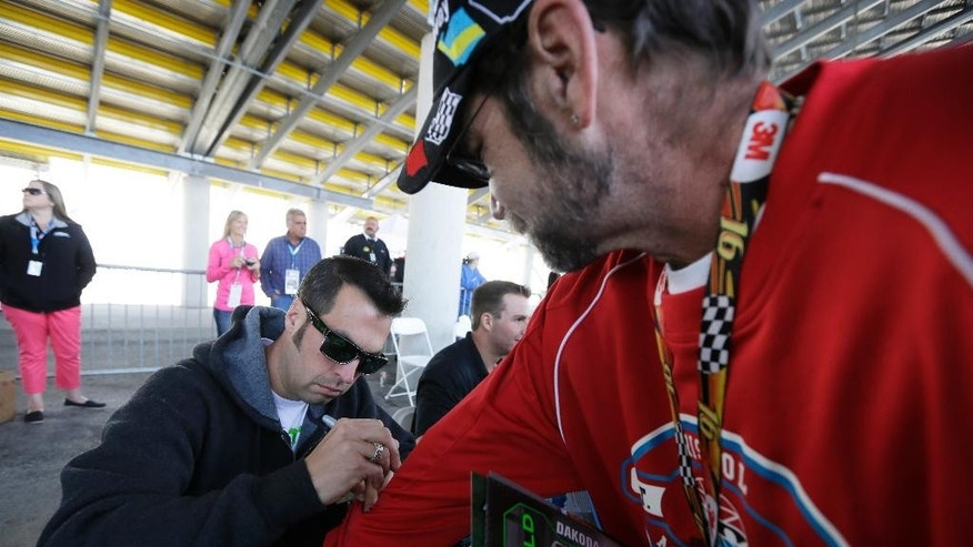 Sam Hornish Jr. autographs a shirt for David Hales, of La Salle, Ill., right, before the NASCAR Nationwide auto race, Sunday, May 18, 2014, at Iowa Speedway in Newton, Iowa. (AP Photo/Charlie Neibergall)