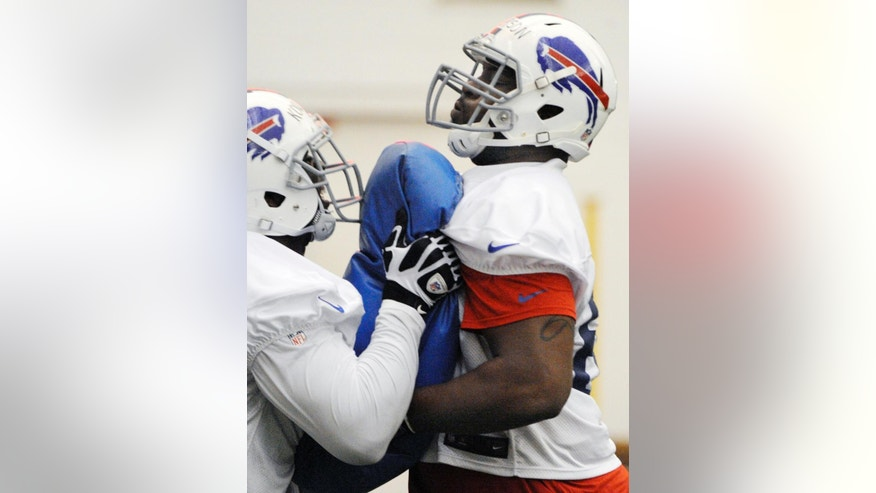 Buffalo Bills' Seantrel Henderson, right, blocks during a drill at an NFL football rookie camp at the team's facility, Sunday, May 18, 2014, in Orchard Park, N.Y. (AP Photo/Gary Wiepert)