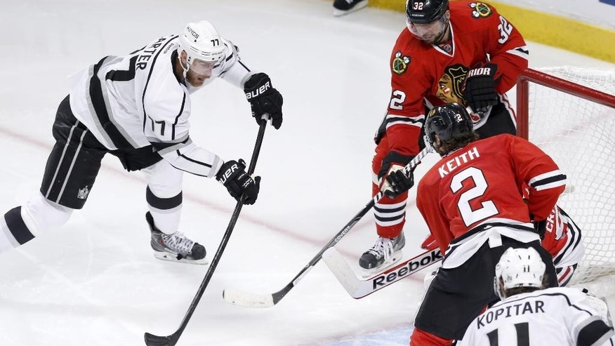 Los Angeles Kings center Jeff Carter shoots, but is unable to score past a defensive wall of Chicago Blackhawks' Michal Rozsival (32)  Corey Crawford and Duncan Keith, during the third period of Game 1 of the Western Conference finals in the NHL hockey Stanley Cup playoffs in Chicago. The Blackhawks' defense is playing a key role in this postseason run as the Kings found out how hard it is to score on the defending Stanley Cup champions. (AP Photo/Charles Rex Arbogast)