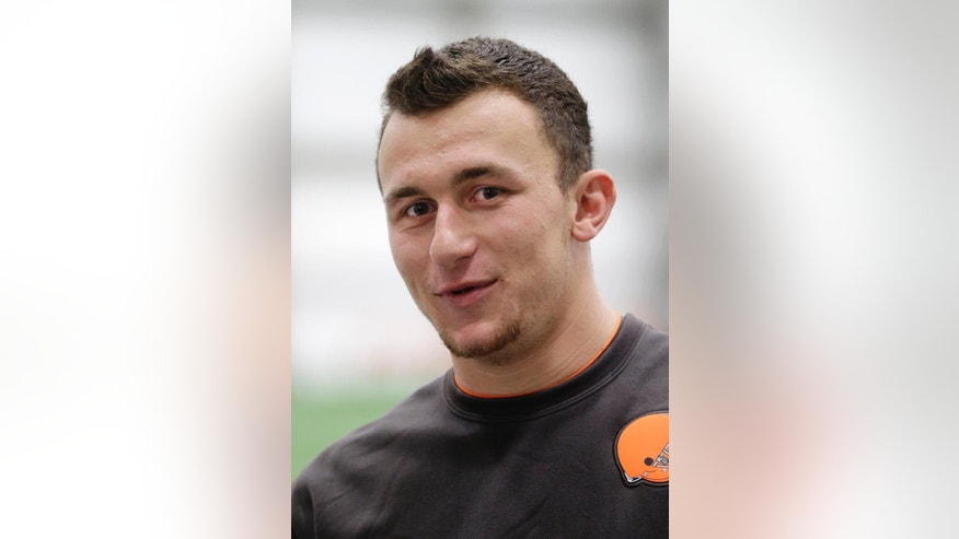 In this pool photo provided by the Cleveland Browns, quarterback Johnny Manziel talks with reporters after a workout at NFL football rookie minicamp at the team's facility in Berea, Ohio Saturday, May 17, 2014. (AP Photo/Cleveland Browns, John Reid, Pool)