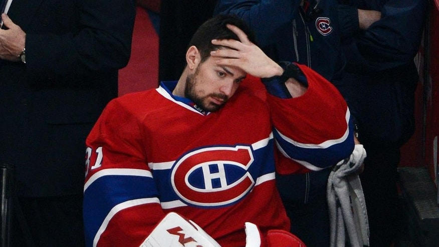 In this May 17, 2014 photo, Montreal Canadiens goalie Carey Price (31) watches from the bench during the third period in Game 1 of the Eastern Conference finals in the NHL hockey Stanley Cup playoffs in Montreal. Price's status for Game 2 of the Eastern Conference final is still unclear. Price briefly tested his right knee Sunday, May 18, 2014, before the Canadiens' optional practice. Coach Michel Therrien said the team will know more Monday before they host the New York Rangers trailing 1-0 in the series. (AP Photo/The Canadian Press, Ryan Remiorz)