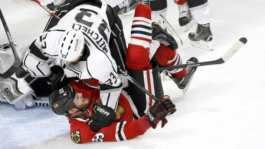 Los Angeles Kings defenseman Willie Mitchell (33) falls over Chicago Blackhawks left wing Bryan Bickell in front of the Kings' net during the third period of Game 1 of the Western Conference finals in the NHL hockey Stanley Cup playoffs in Chicago on Sunday, May 18, 2014. The Blackhawks won 3-1. (AP Photo/Charles Rex Arbogast)