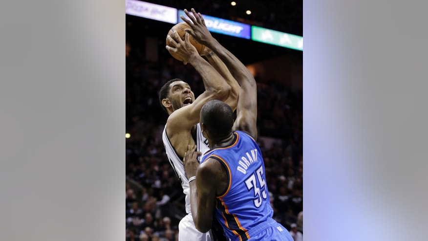 San Antonio Spurs' Tim Duncan, left, shoots over Oklahoma City Thunder's Kevin Durant (35) during the first half of Game 1 of a Western Conference finals NBA basketball playoff series, Monday, May 19, 2014, in San Antonio. (AP Photo/Eric Gay)