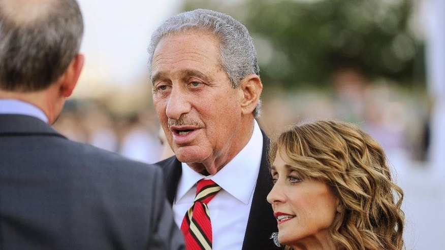 Atlanta Falcons owner Arthur Blank, center, and finance Angie Macuga mingle during the ground breaking ceremony for the new stadium to be the home of the Atlanta Falcons, and the new Atlanta Major League Soccer team franchise, held Monday, May 19, 2014, in Atlanta. (AP Photo/John Amis)