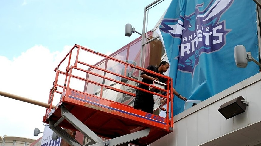 Installer Mariano Simmons positions a new Charlotte Hornets sign outside of Time Warner Cable Arena on Monday, May 19, 2014, in Charlotte, N.C. In preparation for Tuesday's official name change, the Charlotte Bobcats began branding Time Warner Cable Arena with Charlotte Hornets signs. (AP Photo/The Charlotte Observer, Jeff Siner)