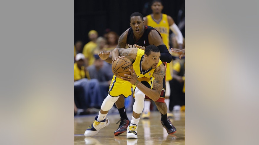 Indiana Pacers' George Hill is defended by Miami Heat's Mario Chalmers during the first half of Game 2 of the NBA basketball Eastern Conference finals in Indianapolis, Tuesday, May 20, 2014. (AP Photo/Michael Conroy)