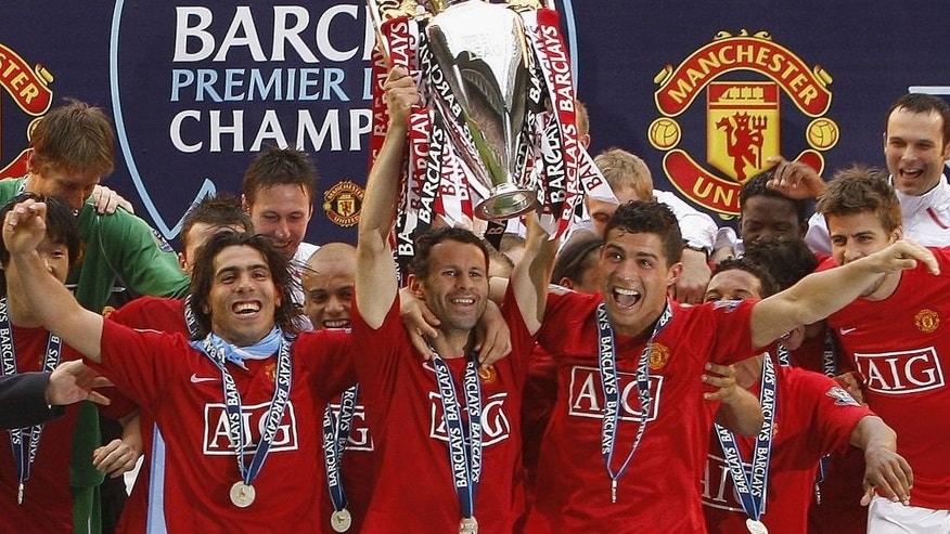 FILE - In this Sunday, May 11, 2008 file photo, Manchester United's, Ryan Giggs, center, lifts the trophy as his team celebrate winning the English Premier League after their 2-0 win against Wigan in their English Premier League soccer match at The JJB Stadium, Wigan, England. At left is Carlos Tevez and at right Cristiano Ronaldo. Manchester United great Ryan Giggs has ended his playing career after a club-record 963 appearances. Giggs made the announcement in an open letter on United's website on Monday, May 19, 2014,  the day he was hired as assistant manager to Louis van Gaal. (AP Photo/Jon Super, File)
