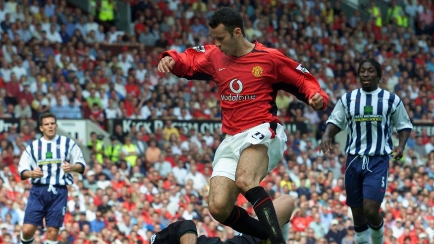 FILE - In this Saturday, Aug. 17, 2002 file photo, Manchester United's Ryan Giggs, top, tackles West Bromwich Albion's keeper Russell Hoult during their English Premier League soccer match at Old Trafford , in Manchester, England. Manchester United great Ryan Giggs has ended his playing career after a club-record 963 appearances. Giggs made the announcement in an open letter on United's website on Monday, May 19, 2014,  the day he was hired as assistant manager to Louis van Gaal.  (AP Photo/Alastair Grant, File)