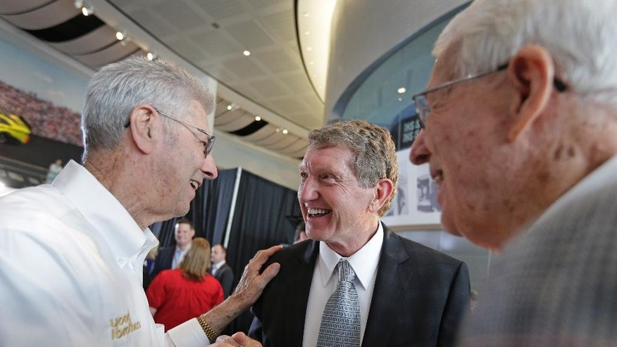 Bill Elliott, center, is congratulated by Leonard Wood, left, and Glen Wood after being named as one of five inductees into the NASCAR Hall of Fame class of 2015, in Charlotte, N.C., Wednesday, May 21, 2014. (AP Photo/Chuck Burton)