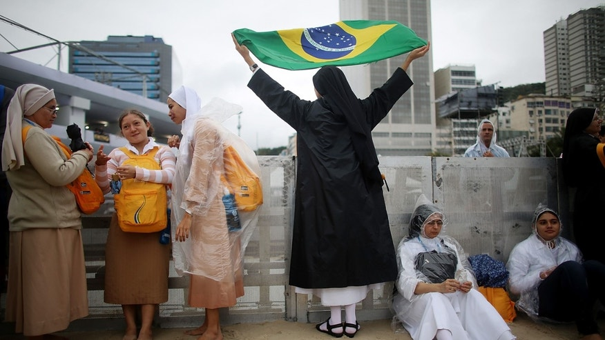 RIO DE JANEIRO, BRAZIL - JULY 23:  Nuns from the Irmas Dominicanas Do Santissimo Sacramento in Sao Paulo, Brazil, wear rain gear as one nun (C) prepares to don a Brazilian flag on Copacabana Beach as they await opening ceremonies for World Youth Day on July 23, 2013 in Rio de Janeiro, Brazil. More than 1.5 million pilgrims are expected to join Pope Francis for his visit to the Catholic Church's World Youth Day celebrations. Pope Francis will deliver his welcome address to the celebrations on July 25 as World Youth Day runs July 23-28.  (Photo by Mario Tama/Getty Images)