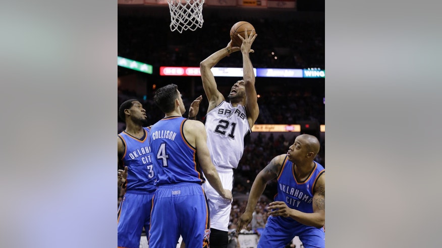 San Antonio Spurs' Tim Duncan (21) shoots over Oklahoma City Thunder's Perry Jones (3) and Nick Collison (4) during the first half of Game 2 of the Western Conference finals NBA basketball playoff series, Wednesday, May 21, 2014, in San Antonio. (AP Photo/Eric Gay)