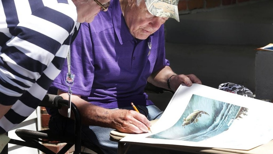 Former Minnesota Vikings head football coach Bud Grant signs a poster during his three-day rummage sale,Thursday, May 22, 2014 at his Bloomington, Minn., home. Grant will be 87 next week. (AP Photo/Jim Mone)