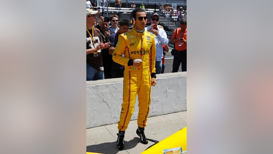 Helio Castroneves, of Brazil, listens to music as he waits for his turn to qualify for the Indianapolis 500 IndyCar auto race at the Indianapolis Motor Speedway in Indianapolis, Sunday, May 18, 2014. (AP Photo/Tom Strattman)