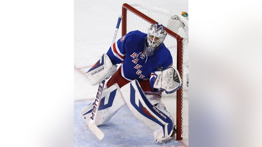New York Rangers goalie Henrik Lundqvist reaches for the puck during the second period of Game 3 of the NHL hockey Stanley Cup playoffs Eastern Conference finals against the Montreal Canadiens, Thursday, May 22, 2014, in New York. (AP Photo/Seth Wenig)