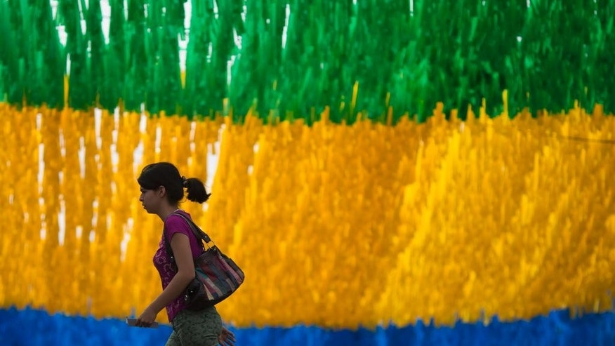 A woman walks on a street decorated for the upcoming World Cup in Manaus, Brazil, Wednesday, May 21, 2014. Manaus is one of the host cities for the 2014 World Cup in Brazil. (AP Photo/Felipe Dana)