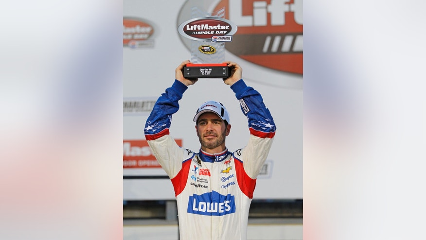 Jimmie Johnson raises the trophy in Victory Lane after winning the pole position during qualifying for Sunday's NASCAR Sprint Cup series auto race at Charlotte Motor Speedway in Concord, N.C., Thursday, May 22, 2014. (AP Photo/Terry Renna)