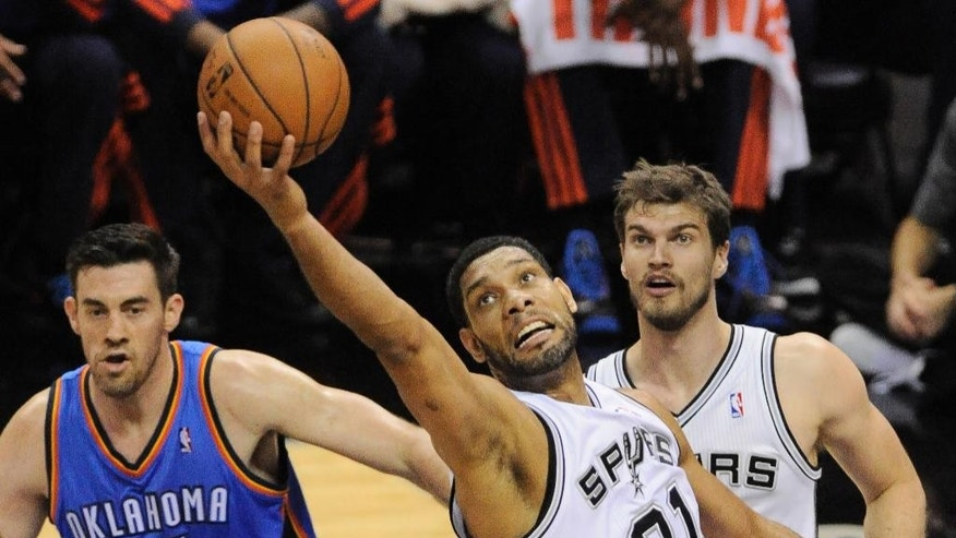 San Antonio Spurs forward Tim Duncan (21) grabs a rebound as Oklahoma City Thunder forward Nick Collison (4) and Spurs forward Tiago Splitter, of Brazil, watch during the first half of Game 2 of the Western Conference finals NBA basketball playoff series, Wednesday, May 21, 2014, in San Antonio. (AP Photo/Darren Abate)