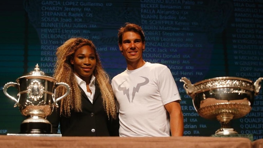 Defending champions Serena Williams, of the U.S, left, and Spain's Rafael Nadal pose during the draw for the French Open Tennis tournament, at the Roland Garros stadium in Paris, Friday, May 23, 2014. The French Open tennis tournament starts Sunday. At left is the women's trophy, at right, the men's trophy. (AP Photo/Michel Euler)