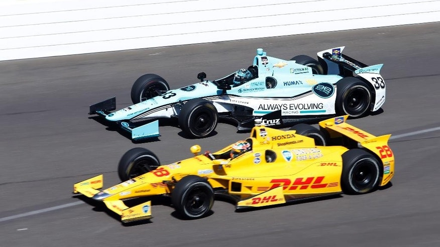 Ryan Hunter-Reay, bottom and James Davison, of Australia, head into the first turn on the final day of practice for the Indianapolis 500 IndyCar auto race at the Indianapolis Motor Speedway in Indianapolis, Friday, May 23, 2014. The 98th running of the Indianapolis 500 is Sunday. (AP Photo/Tom Strattman)