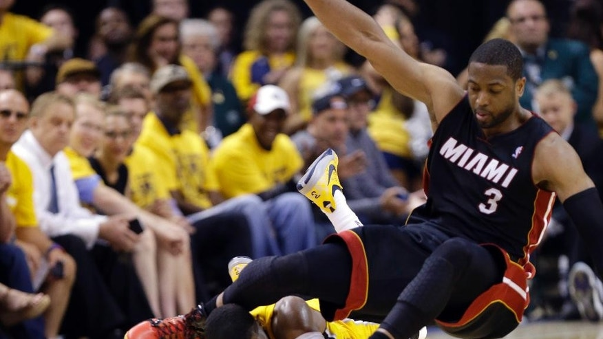 In this Tuesday, May 20, 2014, photo, Indiana Pacers forward Paul George lies on the floor as the knee of Miami Heat guard Dwyane Wade (3) makes contact with his head as they went for a loose ball during the fourth quarter of Game 2 of the NBA basketball Eastern Conference finals in Indianapolis. George has a concussion from the play, and it's unclear when he will return to practice or whether he will play Saturday night against Miami. (AP Photo/Michael Conroy)