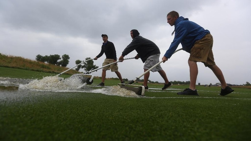 Grounds crew members CJ Watson, Trey Bishop and Payton Neufeld roll water to a drain on the first fairway during a rain delay in the first round of the NCAA men's golf championship Friday, May 23, 2014, at Prairie Dunes Country Club in Hutchinson, Kan. (AP Photo/The Hutchinson News, Travis Morisse)