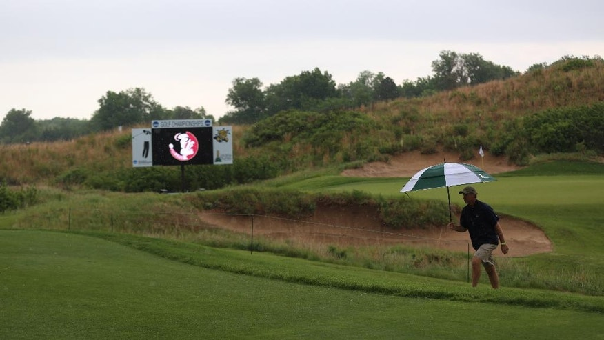 A volunteer makes his way to the clubhouse under the protection of an umbrella during a rain delay in the first round of the NCAA men's golf championship Friday, May 23, 2014, at Prairie Dunes Country Club in Hutchinson, Kan. (AP Photo/The Hutchinson News, Travis Morisse)