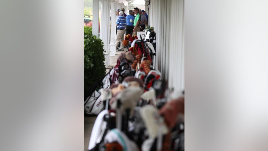 Golfers, volunteers, and spectators stand under an eaves of the clubhouse during a rain delay in the first round of the NCAA men's golf championship Friday, May 23, 2014, at Prairie Dunes Country Club in Hutchinson, Kan. (AP Photo/The Hutchinson News, Travis Morisse)