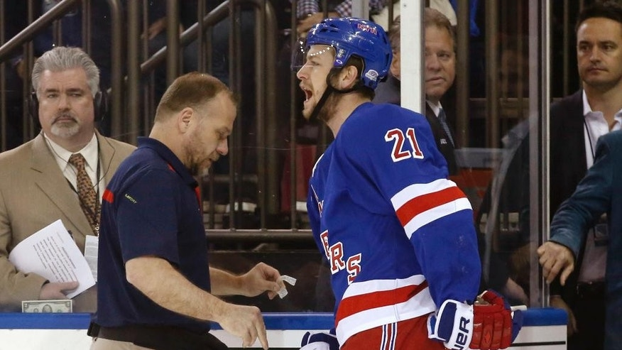 In this May 22, 2014 photo, New York Rangers center Derek Stepan (21) leaves the ice with a member of the Rangers staff after taking a hit from Montreal Canadiens forward Brandon Prust during the first period of Game 3 of the NHL hockey Stanley Cup playoffs Eastern Conference finals in New York. Stepan has a broken jaw and is undergoing surgery. Rangers coach Alain Vigneault made the surprising announcement Friday, May 23, 2014,  on the first of two off days in the series New York leads 2-1. Prust wasn't penalized in the first period of Montreal's 3-2 overtime win Thursday night, but he faces an NHL hearing Friday and a possible suspension. (AP Photo/Kathy Willens)