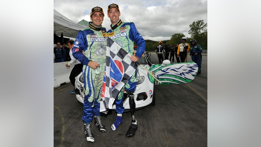 In this photo provided by LAT Photo USA for IMSA,  U.S. Marine Staff Sgt. Liam Dwyer, right, and Tom Long left, pose for a photo after winning the Northeast Grand Prix at Lime Rock Park, Saturday, May 24, 2014, in Lakeville, Conn. Dwyer always knew that despite losing much of his left leg in combat, he could find racing success if he got the chance. That came Saturday when Dwyer teamed with Tom Long to win the ISMA Continental Tire SportsCar Challenge event Saturday. (AP Photo/Scott R LePage, LAT Photo USA for IMSA)