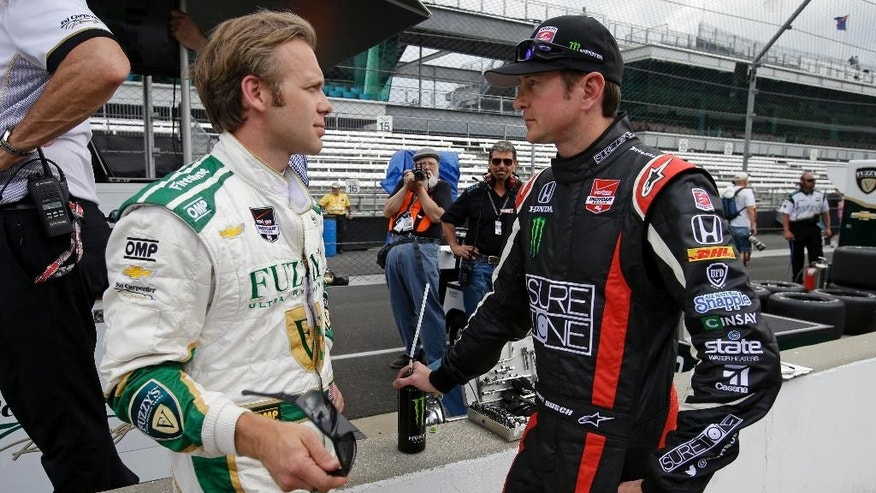 In this photo taken on May 11, 2014, Kurt Busch, right, talks with Ed Carpenter during practice for Indianapolis 500 IndyCar auto race at the Indianapolis Motor Speedway in Indianapolis. Busch will attempt to drive both the Indianapolis 500 and the NASCAR Coca-Cola 600 in Charlotte on Sunday. (AP Photo/Darron Cummings)