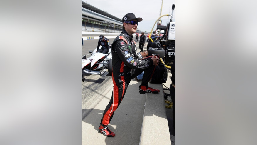 In this May 19, 2014 photo, Kurt Busch stretches before the star of practice for the Indianapolis 500 IndyCar auto race at the Indianapolis Motor Speedway in Indianapolis. Busch will attempt to drive both the Indianapolis 500 and the NASCAR Coca-Cola 600 in Charlotte, NC. on Sunday.  (AP Photo/Michael Conroy)