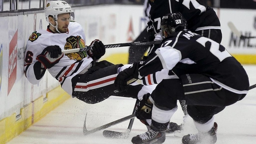 Chicago Blackhawks center Marcus Kruger, left, is checked by Los Angeles Kings defenseman Alec Martinez, and left wing Tanner Pearson, top, during the first period of Game 3 of the Western Conference finals of the NHL hockey Stanley Cup playoffs in Los Angeles, Saturday, May 24, 2014. (AP Photo/Chris Carlson)