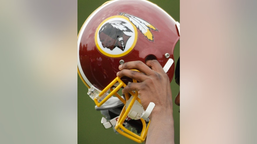 FILE - In this May 1, 2009 file photo, Washington Redskins Marko Mitchell puts his helmet on during their NFL football minicamp practice at their training facility in Ashburn, Va. Half of the U.S. Senate says it's time to change the name of the Washington Redskins. Forty-nine Democratic senators wrote NFL Commissioner Roger Goodell on Thursday, May 22, 2014. They say racism and bigotry do not belong in professional sports.  (AP Photo/Alex Brandon, File)