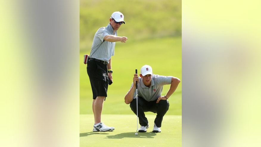 Stanford coach Phil Row, left, helps Patrick Rodgers read the sixth green during the second round of the NCAA college men's golf championship on Saturday, May 24, 2014, at Prairie Dunes Country Club in Hutchinson, Kan. (AP Photo/The Hutchinson News, Travis Morisse)