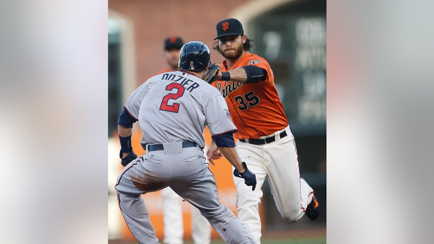 San Francisco Giants shortstop Brandon Crawford (35) tags out  Minnesota Twins' Brian Dozier (2) as he tried to steal third base in the first inning of a baseball game Friday, May 23, 2014, in San Francisco. (AP Photo/Tony Avelar)