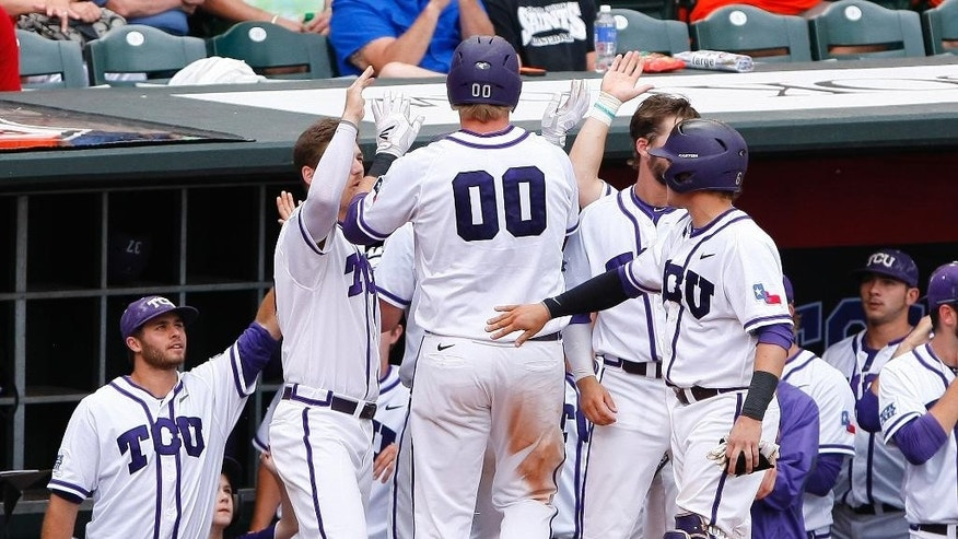 TCU's Kevin Cron (00) celebrates with his team after scoring a run in the third inning of the championship game against Oklahoma State in the Big 12 conference NCAA college baseball tournament in Oklahoma City, Sunday, May 25, 2014. (AP Photo/Alonzo Adams)