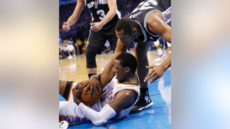 San Antonio Spurs forward Boris Diaw (33) reaches for the ball held by Oklahoma City Thunder guard Reggie Jackson (15) in the second quarter of Game 3 of an NBA basketball playoff series in the Western Conference finals, Sunday, May 25, 2014, in Oklahoma City. (AP Photo/Sue Ogrocki)