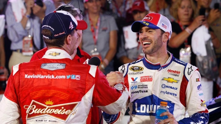 Jimmie Johnson, right, is congratulated by Kevin Harvick, left, after winning the NASCAR Sprint Cup series Coca-Cola 600 auto race at Charlotte Motor Speedway in Concord, N.C., Sunday, May 25, 2014. (AP Photo/Terry Renna)
