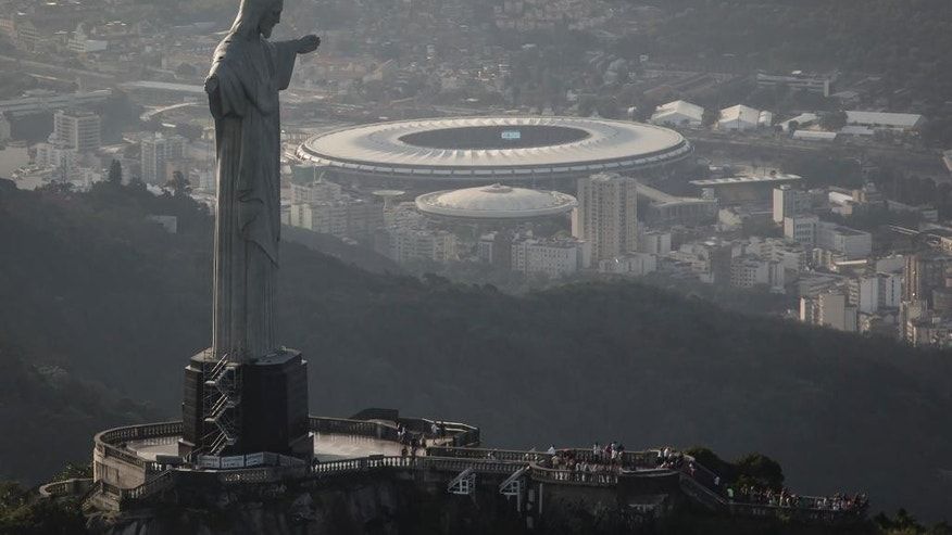 In this May 13, 2014, photo,This aerial view shot through an airplane window shows the Maracana stadium behind the Christ the Redeemer statue in Rio de Janeiro, Brazil. As opening day for the World Cup approaches, people continue to stage protests, some about the billions of dollars spent on the World Cup at a time of social hardship, but soccer is still a unifying force. The international soccer tournament will be the first in the South American nation since 1950. (AP Photo/Felipe Dana, File)