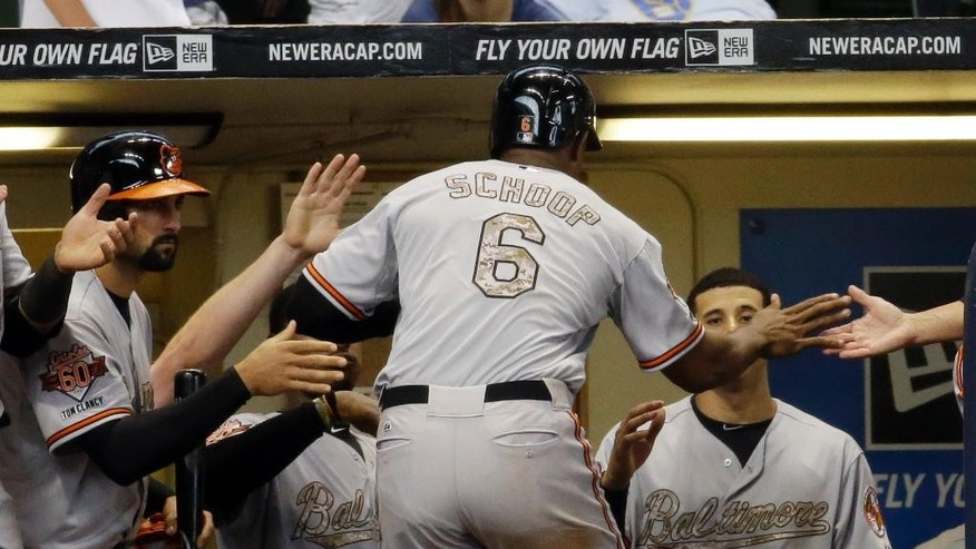 Baltimore Orioles' Jonathan Schoop is congratulated after hitting a home run during the ninth inning of a baseball game against the Milwaukee Brewers Monday, May 26, 2014, in Milwaukee. (AP Photo/Morry Gash)