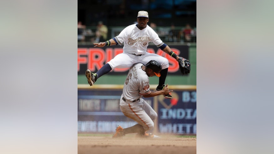 Milwaukee Brewers shortstop Jean Segura (9) leaps over Baltimore Orioles' Jonathan Schoop to turn a double play on a ball hit by Nick Markakis during the fourth inning of a baseball game Monday, May 26, 2014, in Milwaukee. (AP Photo/Morry Gash)