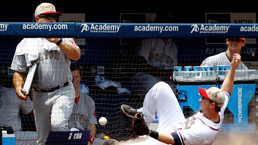 Atlanta Braves' Chris Johnson (23) nearly misses catching a foul ball as he slides towards the Boston Red Sox dugout during the second inning of a baseball game on Monday, May 26, 2014, in Atlanta, Ga. (AP Photo/Butch Dill)
