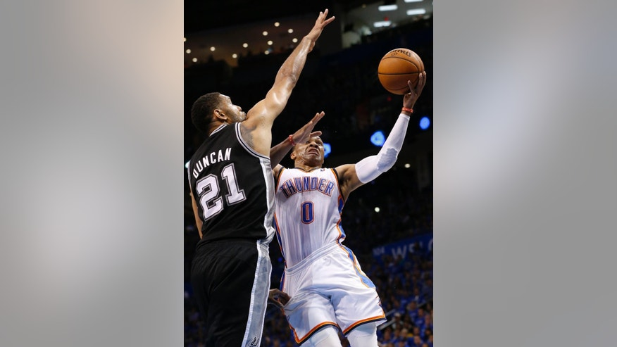 Oklahoma City Thunder guard Russell Westbrook (0) shoots in front of San Antonio Spurs forward Tim Duncan (21) in the second quarter of Game 3 of an NBA basketball playoff series in the Western Conference finals, Sunday, May 25, 2014, in Oklahoma City. (AP Photo/Sue Ogrocki)
