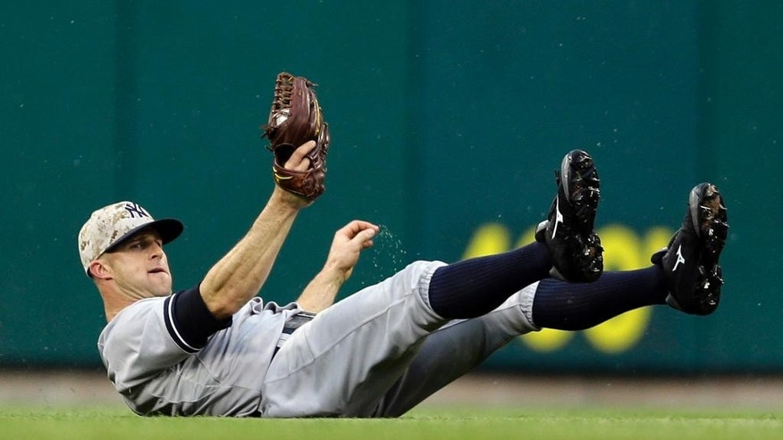 New York Yankees left fielder Brett Gardner slides after catching a fly by St. Louis Cardinals' Matt Holliday for an out during the first inning of a baseball game Monday, May 26, 2014, in St. Louis. (AP Photo/Jeff Roberson)
