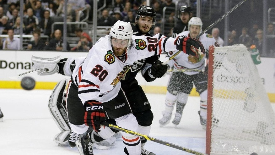 Chicago Blackhawks left wing Brandon Saad, left, and Los Angeles Kings defenseman Slava Voynov go after the puck during the first period of Game 4 of the Western Conference finals of the NHL hockey Stanley Cup playoffs in Los Angeles, Monday, May 26, 2014. (AP Photo/Chris Carlson)